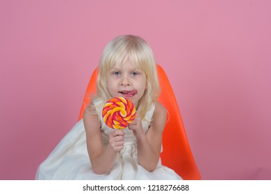 Unstoppable giant lollipop. Happy candy girl. Small girl hold lollipop on stick. Small child with sweet lollipop. Happy childhood food.