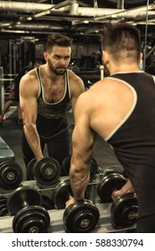 Unstoppable in sports. Vertical shot of a strong young handsome fitness man looking in the mirror fiercely and seriously taking heavy weights for a workout at the gym bodybuilding motivation strength