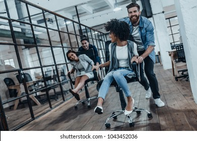 Unstoppable team! Four young cheerful business people in smart casual wear having fun while racing on office chairs and smiling