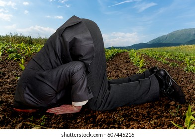 Unsuccessful businessman burying his head in the ground