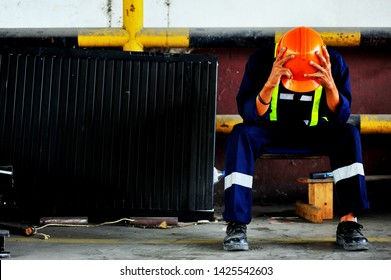 Unsuccessful foreman feels terrible and a hand on the head with sitting on a chair in the construction site.