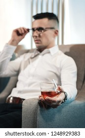 Unsuccessful meeting. Exhausted young rich ceo drinking whisky after unsuccessful meeting