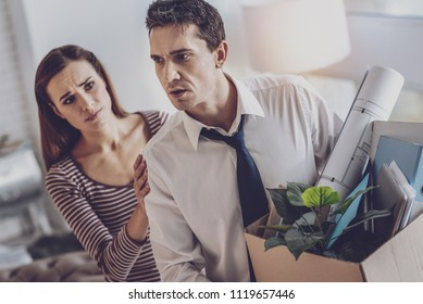 Unsuccessful period. Depressed cheerless man standing near his wife while thinking about his unsuccessful life