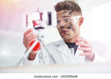 Unsuccessful time. Close up of blonde-haired student wearing glasses having dirty face after unsuccessful chemistry experiment