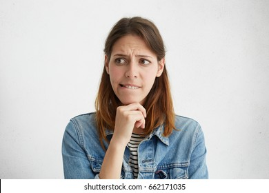 Unsure cute woman in casual clothes holding hand under chin biting lip looking aside while deciding what to do. Uncertain female frowning her face having thoughtful expression isolated over white wall