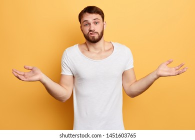 Unsure doubtful puzzled bearded man wearing white T-shirt shrugging his shoulders in questioning gesture, man has regretful clueless look. difficult situation