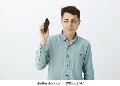 Unsure handsome and funny guy with short dark hair, holding smartphone away form ear and staring unsure at device, listening mom yelling at him, standing doubtful and awkward over gray wall