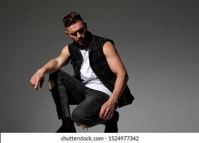 Unsure man curiously looking to the side and squatting while wearing black jeans and jeans vest on gray studio background