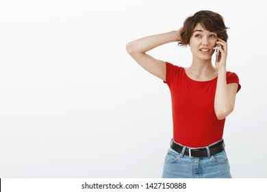 Unsure puzzled cute girl making order phonecall hold smartphone ear scratch head uncertain doubting look up thoughtful pondering confused how answer standing white background hesitant