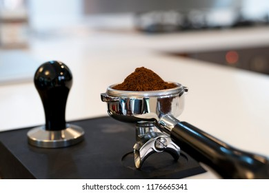 Un-tamped coffee grounds in a silver portafilter on a black tamper mat