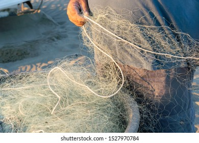 Untangling the net. Fishermen pulling and mending the traditional fishing nets by hand