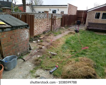 Untidy back garden with rubbish and lumpy green grass