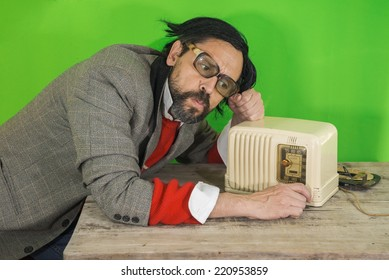 An untidy bizarre man, wearing big patched glasses and a toupee, listening to a station on an antique bakelite tube radio on scratched wooden table, over green background
