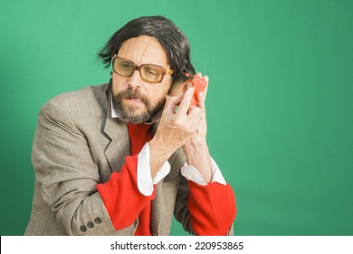 An untidy bizarre man, wearing big patched glasses and a toupee, trying to tune in a station on an antique plastic transistor radio, over green background