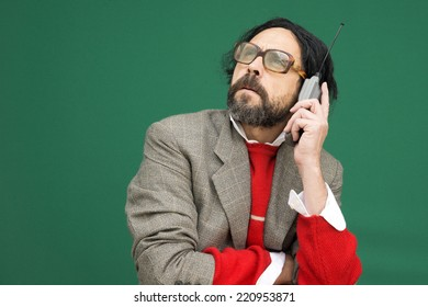 An untidy bizarre man, wearing big patched glasses and a toupee, trying to answer an incoming phone call on an antique big cellphone, over green background