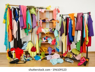 Untidy cluttered woman wardrobe with colorful clothes and accessories. Messy clothes thrown on a shelf, on the ground and off the hangers and racks.