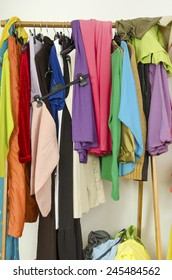 Untidy cluttered woman wardrobe with colorful clothes and accessories. Messy clothes thrown off the hangers.