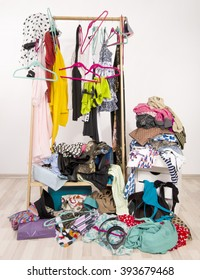 Untidy cluttered woman wardrobe with colorful clothes and accessories. Messy rack of clothes and hangers with a big pile thrown on the ground.