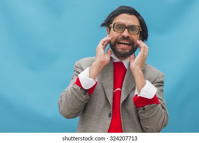 An untidy man, wearing broken glasses, expressing horror, over light blue background