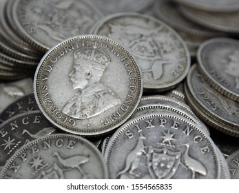 "Untidy pile of old Australian sterling silver Sixpence coins, also known as a ""Half Shilling"" or a ""Zac"". Bearing the Southern Cross coat of arms on the reverse and King George V and VI on the obverse"