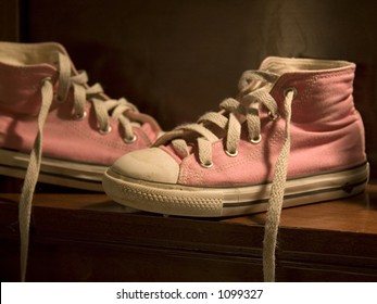 Untied Pink Chuck Taylors High tops on bench