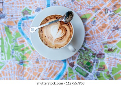 Untouched fresh cappuccino coffee with heart design in the foam and spoon across on top of out of focus blurred tourist city map of Rome, Italy