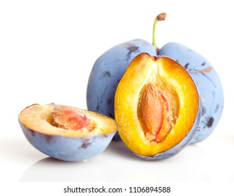 Untouched plum fruit with original color streight from tree, one plum divided in half