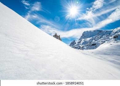 Untouched snow slopes on a sunny day with blue sky in alpine mountains, France