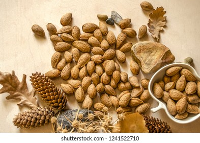 Untreated almonds in a white faience cup and on a wooden table among pebbles, cones and autumn leaves