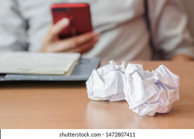 Unused crumpled papers on the desk with asian business man looking smartphone for relaxation during work at office. No idea in business concept, job boring concept. Selective focus.