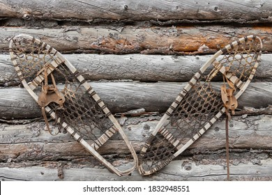 Unused and neglected snowshoes hang on the weathered sides of an abandoned Trappers Cabin in the Northwest Territories of Canada