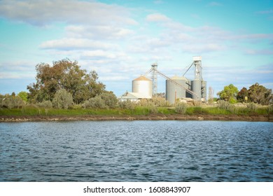 The unused silos of Pyramid Hill in central Victoria, Australia with large dam full of water in the foreground.