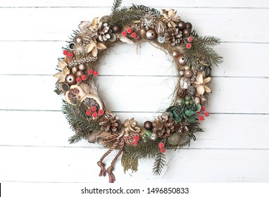 Unusial handmade Christmas wreath with golden, copper, brown, green decorations and red berries on a white wooden background