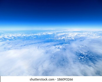 Unusual aerial view of clouds and blue skies above the earth.