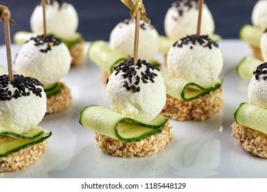 An unusual beautiful appetizing appetizer for a festive table. Mini canapes from a piece of baguette with sesame, thin slice of cucumber and a ball of cheese. Exotic black sesame for decoration.