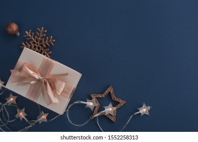 Unusual Christmas gift on stylish dark blue background with copy space for text , top view flat lay design composition