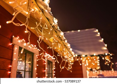 unusual christmas wreath on window. luxury decorated store front with garland lights in european city street at winter seasonal holidays