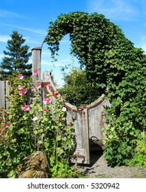 Unusual circular wooden garden gate with hollyhock flowers.