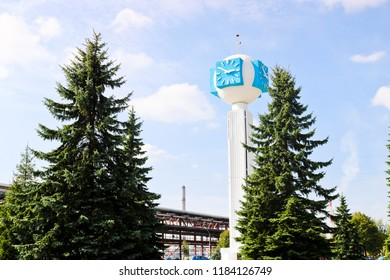 Unusual clock on a background of a white-blue sky. A clock in the form of a molecule, an atom. On chemical production, a watch-column, a clock tower in a spruce forest. Backdrop of chemical pipelines.