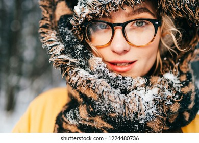Unusual cute girl creative lifestyle fashion pottrait. Odd strange lovely funny woman in glasses. Graceful beatiful female smiling sensual face. Bizzare rebel lady wearing winter clothes. Snowy scarf