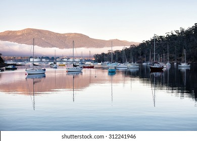 Unusual fog bank drifts down the Derwent River, Hobart, Tasmania, with Mount Wellington in background and Geilston Bay yacht harbour in foreground
