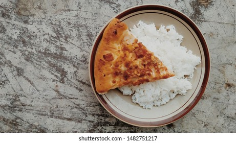 Unusual Food, combination of a slice pizza with white rice. One unusual food is a combination of pizza and white rice.