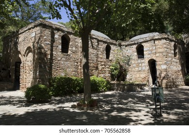 an unusual foreshortening of the Catholic stone shrine of the House of the Virgin Mary, surrounded by trees in the ancient city of Ephesus
