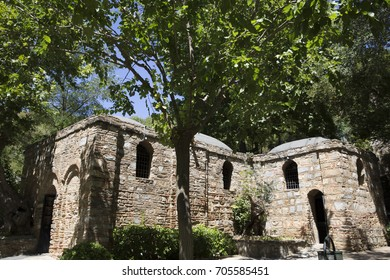 an unusual foreshortening of the Catholic stone shrine of the House of the Virgin Mary in the shadow of tall trees in the ancient city of Ephesus on a summer day