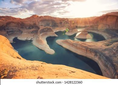 Unusual natural background. Reflection Canyon on Lake Powell, Utah, USA. Inspiring hiking scene-man resting on the beautiful sunset point.