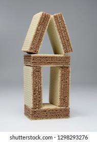 Unusual original house made of square waffle chocolate bars. Close-up.