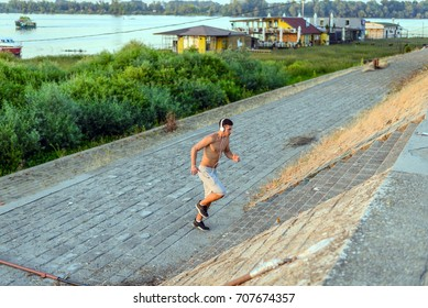 Unusual point of view. Sport, lifestyle concept, copy space.Sportsman jogging in the forest. Healthy lifestyle.Handsome male, jogging in the park, wearing headphones, listening music.