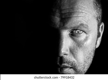 Unusual portrait of male face half hidden in shadows with visible eye pupil replaced by man's distorted face