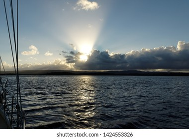 An unusual stratocumulus cloud Sunrise Seascape with crepuscular rays over grey sea water with clear reflections.Queensland, Australia.