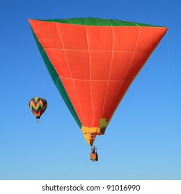 Unusual triangle-shaped hot air balloon with second balloon in distance